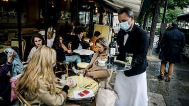 Un serveur à la terrasse de l'établissement des Deux Magots à Paris, le 19 mai 2021.
