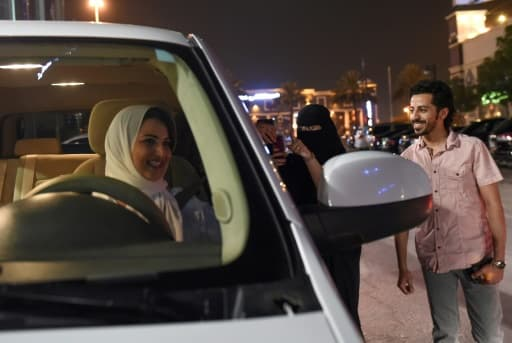 Une Saoudienne filme et apporte son soutien à Samar Al-Moqren (G) au volant de sa voiture à Ryad le 24 juin 2018, jour de la levée de l'interdiction aux femmes de conduire