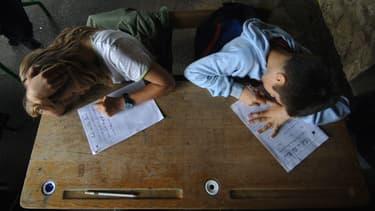 Des élèves de CM2 écrivent une dictée en juin 2007 sous le préau de l'école primaire du Puits Picard, à Caen (photo d'illustration)