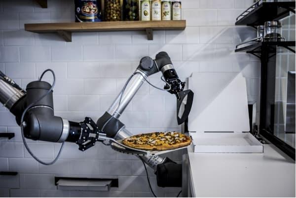 Le robot prédécoupe la pizza une fois déposée dans son carton.