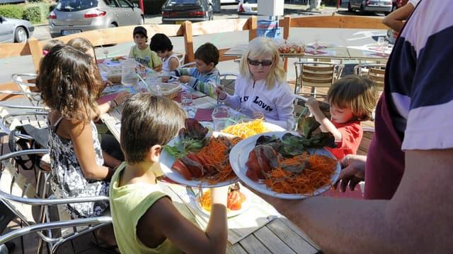 """Des enfants déjeunent le 12 septembre 2011 dans un restaurant du centre-ville de Thonon-les-Bains, invités par des commerçants """"outrés"""" par la décision du maire de restreindre l'accès à la cantine des enfants de chômeurs."""