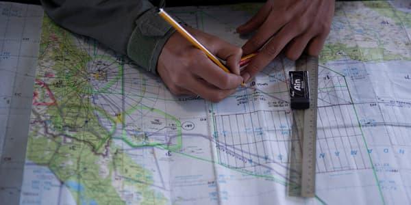 Un membre de l'armée de l'air malaisienne tente de retrouver la trace du Boeing 777 sur une carte marine, le 14 mars 2014.