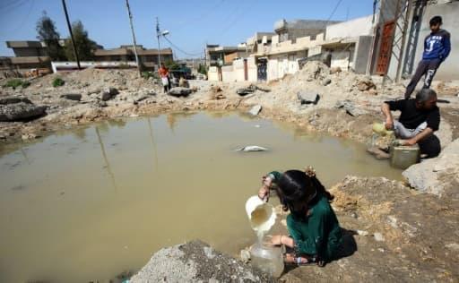 Des habitants de Mossoul remplissent des bidons d'eau, le 6 avril 2017 en Irak