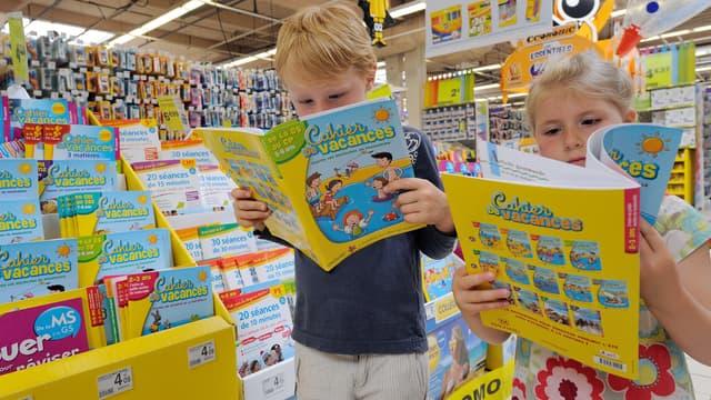 Des enfants feuillettent un cahier de vacances à Englos, en 2013