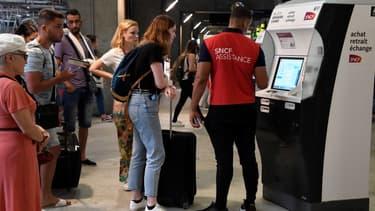 Un agent de la SNCF aide des voyageurs dans la gare Montparnasse, le 28 juillet 2018, alors que la circulation est fortement perturbée par une panne électrique.