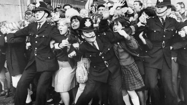 Des fans des Beatles sont contenus par la police devant les grilles du Palais de Buckingham, lors d'une apparition publique du groupe, reçu par la reine, le 26 octobre 1965 à Londres.