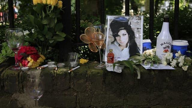 Fleurs et objets déposés devant le domicile d'Amy Winehouse après sa mort, en juillet. La fondation créée après la mort de la chanteuse britannique va financer une bourse à l'école de chant de Londres où son talent a été découvert. /Photo prise le 24 juil