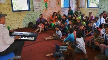 Un mois après le séisme dévastateur, des écoliers népalais entonnent une chanson autour de leur professeur, le 31 mai à Bhaktapur, près de Katmandu.