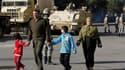 Une famille passe à proximité de soldats dans le centre du Caire. L'armée égyptienne a promos de ne pas ouvrir le feu sur les manifestants hostiles au président Hosni Moubarak. Le vice-président, issu des rangs de l'armée, a pour sa part annoncer l'ouvert