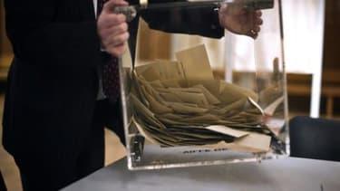 Un scrutateur vide l'urne contenant les bulletins de vote, le 20 mars 2011 à Dijon