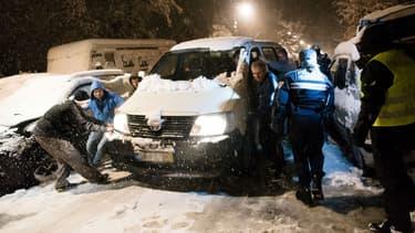 Des automobilistes tentent de déplacer un camion coincé dans la neige, le 7 février 2018 à Bièvres (Essonne)