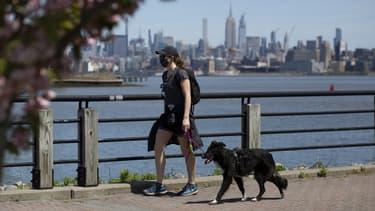 Une femme promenant son chien en portant un masque à Jersey City, près de New York.