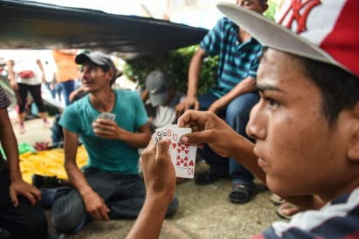 "Des migrants honduriens jouent aux cartes à Mapastepec (sud du Mexique), le 24 octobre 2018.   Thousands of mainly Honduran migrants heading to the United States, a caravan President Donald Trump has called an ""assault on our country"", c..."