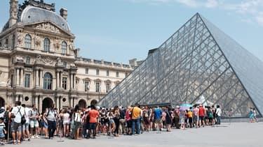 Des visiteurs faisant la queue devant la pyramide du Louvre.
