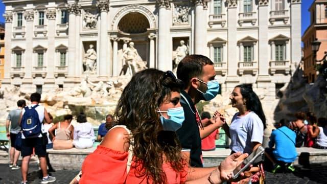 Des touristes le 19 août 2020 devant la Fontaine de Trevi à Rome: depuis lundi, le port des masques est  obligatoire en Italie le soir dans les lieux publics fréquentés