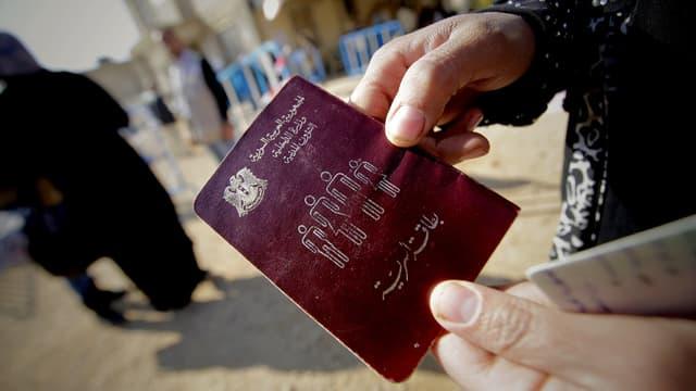 Une femme syrienne tenant son passeport à la main.