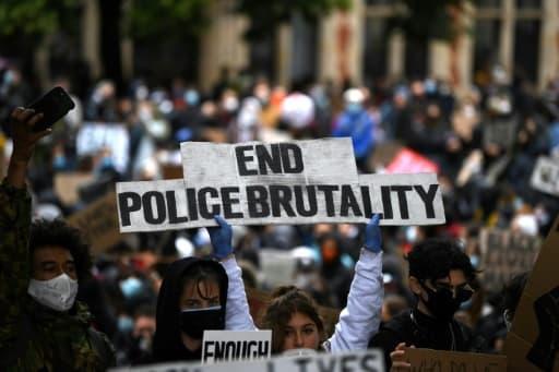 """""""Mettons fin à la brutalité policière"""", clame une pancarte au milieu de la manifestation qui s'est tenue devant le Parlement à Londres, le 6 juin 2020"""