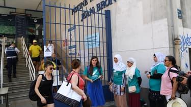 Une quinzaine de personnes, appartenant majoritairement au collectif Alliance Citoyenne, se sont rassemblé devant la piscine Jean Bron de Grenoble.
