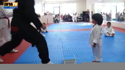 Un petit garçon essaie de casser une planche au taekwondo