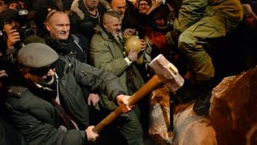 Des manifestants renversent une statue de Lénine, le 8 décembre, à Kiev, en Ukraine.