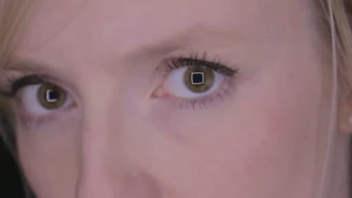 Une joueuse de PS4 avec des carrés dans les yeux, un des quatre symboles de la PLaystation avec les ronds, les triangles et les croix...