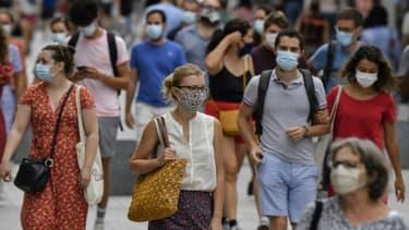 Des piétons portant un masque de protection dans une rue de Lyon le 22 août 2020