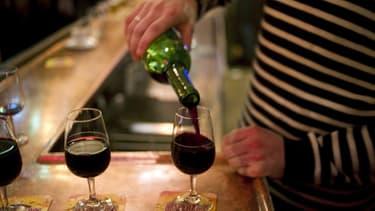 Un homme en train de servir des verres de vin rouge.