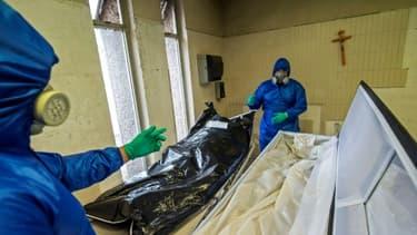 Des employés de Los Olivos Funerales en combinaison intégrale de protection s'occupent du corps d'une personne décédée du coronavirus, le 1er juin 2020 à Mexico