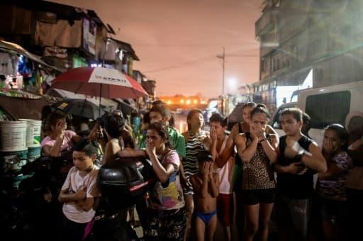 Les 28 septembre 2016 à Manille, habitants de Manille sidérés devant trois morts, victimes de la lutte antidrogue aux Philippines