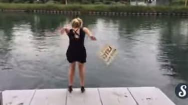 """Une jeune femme s'apprêtant à sauter à l'eau dans le cadre du défi """"à l'eau ou au resto""""."""