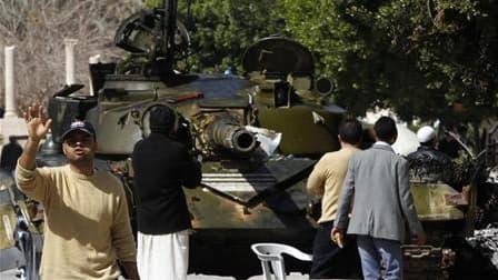 Des rebelles rassemblés autour d'un char utilisé par des soldats de l'armée libyenne ayant fait défection, dans le centre de Zaouïah, samedi. Les insurgés libyens disent avoir repoussé dimanche un nouvel assaut des forces fidèles à Mouammar Kadhafi sur le