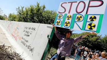Un homme portant une pancarte sur le site de Bure, où doit être installé un site d'enfouissement de déchets nucléaires, le 14 août 2016.