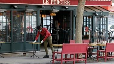 Un employé nettoie des tables sur une terrasse de café à Paris, le 10 mai 2021, avant la réouverture des terrasses au public le 19 mai
