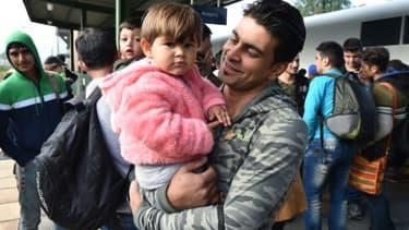 Un migrant, un enfant dans les bras, arrivé en train de Hongrie via Munich, sur le quai de la gare d'Eisenhuettenstadt, dans l'est de l'Allemagne, le 7 septembre 2015