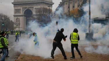 Un manifestant jette un projectile lors du mouvement des gilets jaunes samedi 1er décembre près de l'Arc de Triomphe à Paris.