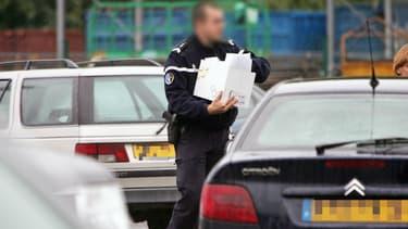 Un gendarme identifie des voitures sur un parking (image d'illustration).