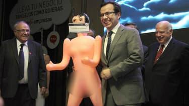 """Sur la bouche de la poupée gonflable offerte au ministre on peut lire """"Pour stimuler l'économie"""""""