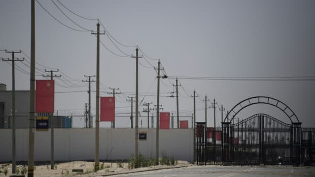 Des drapeaux chinois le long d'une route menant à un centre de rééducation politique où seraient détenus des musulmans ouïghours, le 31 mai 2019 près de Hotan, dans le Xinjiang