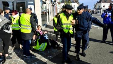 Des forces de l'ordre évacuent des manifestants vêtus d'un gilet jaune dans le cadre d'un rassemblement contre la hausse des prix des carburants, le 9 novembre 2018 à Albert, dans la Somme.