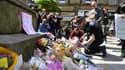 Des passants déposent des fleurs en hommage aux victimes de l'attentat, le 23 mai, dans le centre de Manchester.