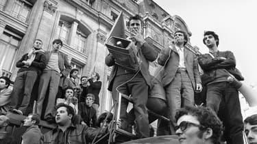 """Jacques Sauvageot, l'un des trois leaders, avec Alain Geismar (1er plan, en bas, avec la veste de cuir) et Daniel Cohn-Bendit (non photographié) de """"Mai 1968"""", et président de l'Unef, micro à la main, harangue des étudiants réunis le 08 juin 1968 devant la Gare Saint-Lazare à Paris."""