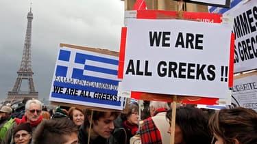 """""""Nous sommes tous des Grecs"""", peut-on lire sur une pancarte brandie par un manifestant place du Trocadéro à Paris. Un millier de personnes ont manifesté samedi à Paris dans le cadre d'une journée internationale de soutien à la population grecque soumise à"""