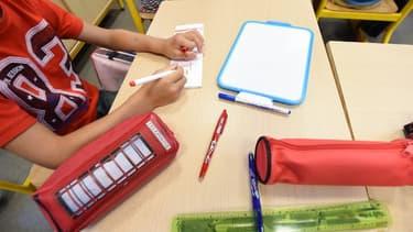 Un enfant écrit son nom sur un bout de papier lors de la rentrée des classes (image d'illustration)