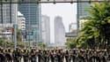 """Soldats thaïlandais marchant en direction du campement des """"chemises rouges"""" dans le centre de Bangkok. La situation est explosive dans le centre de Bangkok après une nuit d'affrontements entre soldats et manifestants antigouvernementaux qui ont fait un m"""