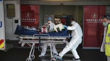 Des ambulanciers transportent au service des urgences de l'hôpital de Strasbourg un patient atteint du coronavirus, arrivé par avion de la région lyonnaise, le 6 novembre 2020