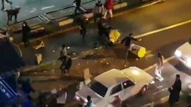 Image extraite d'une vidéo fournie par l'agence iranienne Mehr News montrant un groupe d'hommes tapant dans des plots de circulation dans une rue de Téhéran le 30 décembre 2017