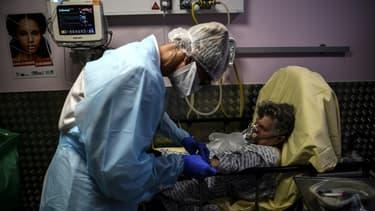 Une infirmière s'occupe d'une personne âgée présentant des symptômes du coronavirus au service des urgences de l'hôpital André Grégoire à Montreuil, le 15 octobre 2020 près de Paris