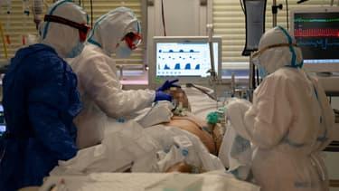 Des soignants en combinaison intégrale de protection s'occupent d'un patient atteint du coronavirus (Photo d'illustration).