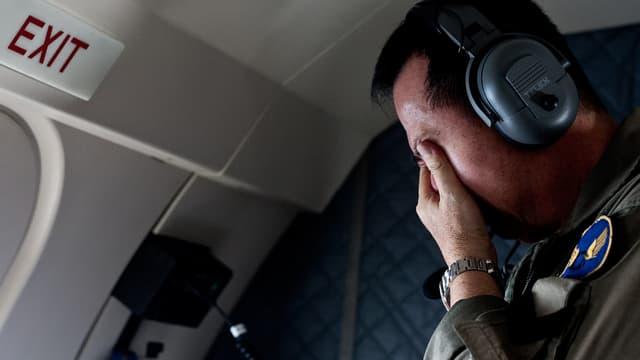 Un membre de la famille d'un des passagers à bord du vol QZ8501 pleure lors d'une opération de recherche de l'armée indonésienne au dessus de la mer de Java, le 30 décembre 2014.