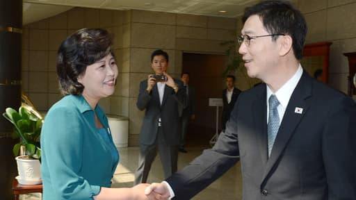 La déléguée de Corée du Nord, à gauche, salue cordialement son homologue du sud, juste avant le début de la réunion Nord-Sud.